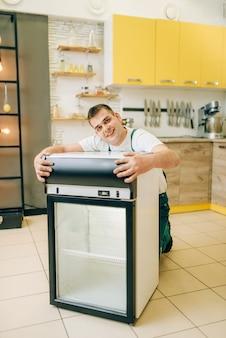 Рабочий в униформе обнимает холодильник дома