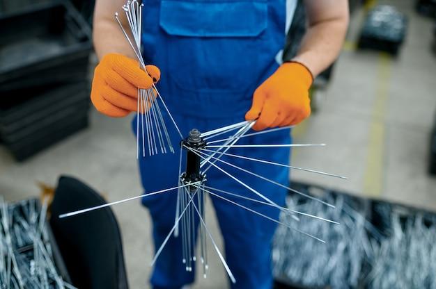 제복을 입은 작업자가 공장에 새 자전거 스포크를 설치합니다. 작업장에서 자전거 바퀴 조립, 사이클 부품 설치