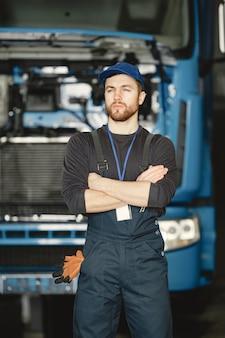 제복을 입은 노동자. 남자는 트럭을 수리합니다. 도구를 가진 남자