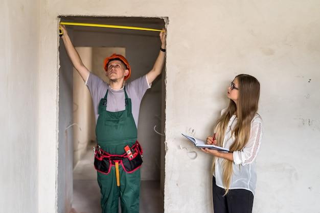 Работник в униформе измерительной двери и женщина, пишущая в блокноте