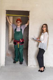 작업자 유니폼 측정 문 및 메모장에서 작성하는 여자