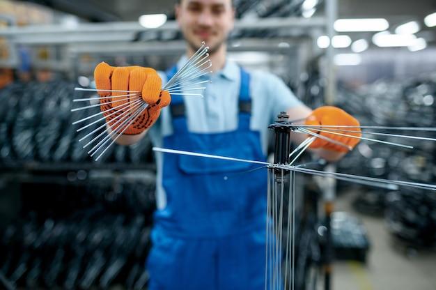 제복을 입은 노동자는 공장에서 새로운 자전거 스포크를 보여줍니다. 작업장에서 자전거 바퀴 조립, 사이클 부품 설치