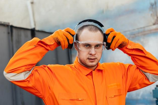 ヘッドフォンと保護メガネを着用した制服を着た労働者