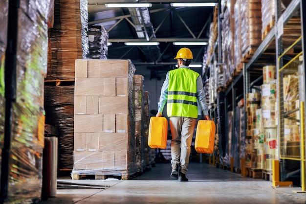 倉庫を歩きながら、油で缶を移動するベストの労働者。