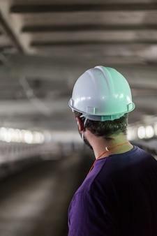 白いヘルメットの労働者は、汚れたほこりの多いワークショップを見てください。