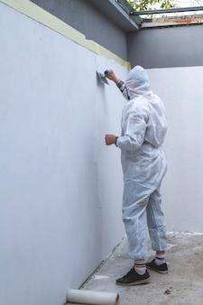 Рабочий в белом защитном комбинезоне оштукатуривает стену