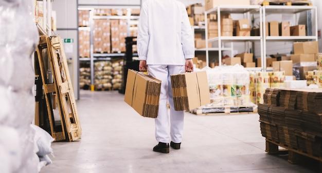 Работник в белых стерильных тканях переносит стопки сложенных коробок в зону хранения.