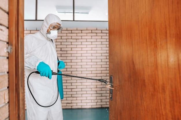 Рабочий в белой стерильной форме, в резиновых перчатках и маске держит распылитель с дезинфицирующим средством и стерилизует двери в школе.