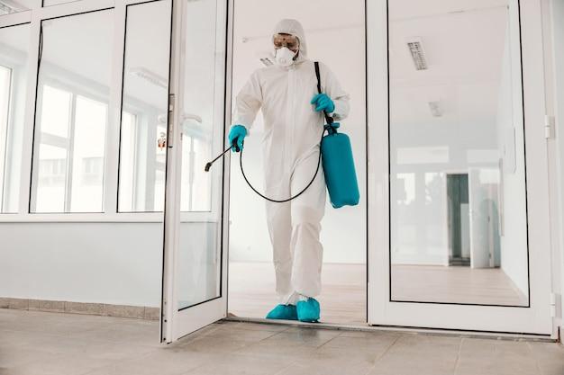 Рабочий в белой стерильной форме, в резиновых перчатках и маске держит распылитель с дезинфицирующим средством и стерилизует школу.