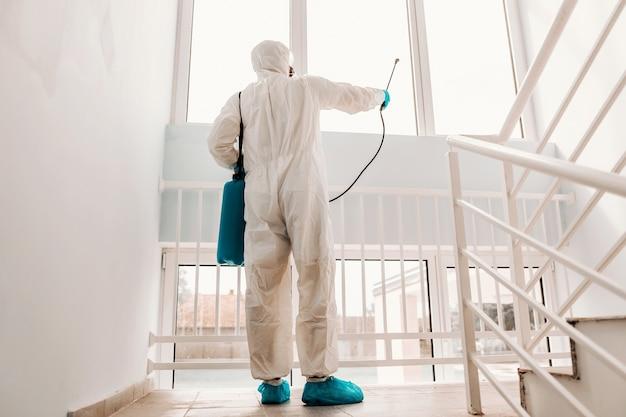 Рабочий в белой стерильной форме, в резиновых перчатках и маске держит распылитель с дезинфицирующим средством и стерилизует окна в школе.