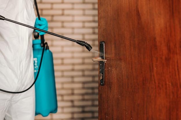 Рабочий в белой стерильной форме, в резиновых перчатках держит распылитель с дезинфицирующим средством и стерилизует двери в школе.