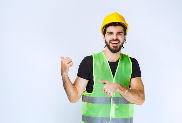 Рабочий в желтом шлеме и шестерне, указывая позади.