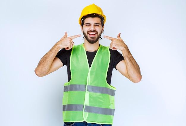 Рабочий в желтом шлеме, указывая на себя.