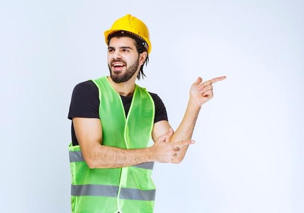 右側を指している黄色いヘルメットの労働者。