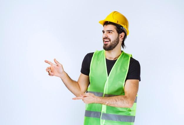 左側を示す黄色いヘルメットの労働者。