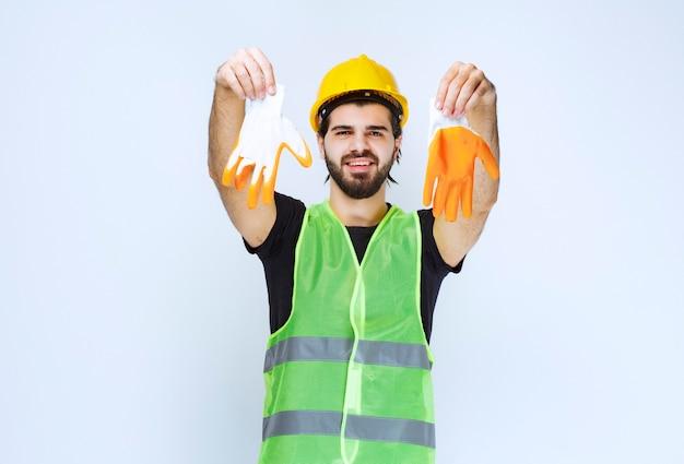 黄色いヘルメットをかぶった労働者が、ワークショップの手袋を取り出してデモンストレーションします。