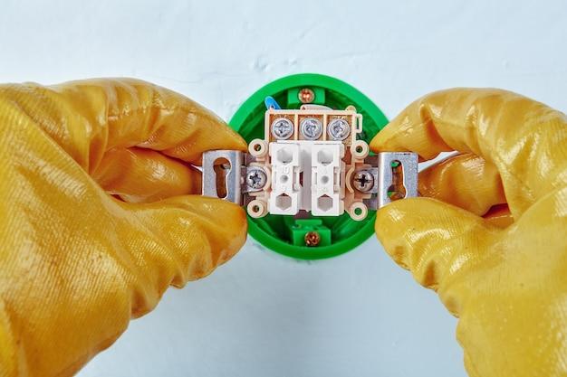Рабочий в желтых защитных перчатках монтирует новую кнопку.