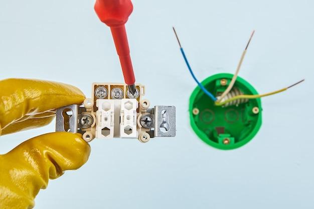 Рабочий в желтых защитных перчатках затягивает винт в двойном выключателе света с круглой электрической коробкой.