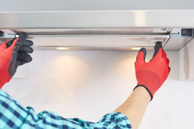 Worker install filter in home range hood at kitchen. handyman removing filter from a exhaust hood. cooker hood repair.