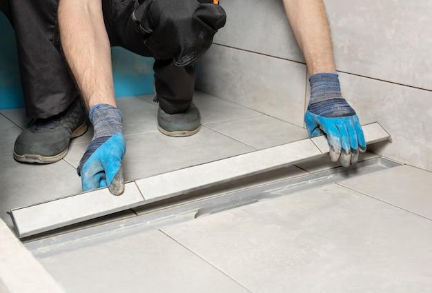 Рабочий, устанавливающий крышку сливного отверстия, украшенную керамической плиткой в ванной комнате