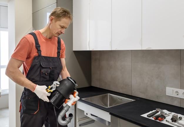 Рабочий, устанавливающий измельчитель бытовых отходов для кухонной мойки