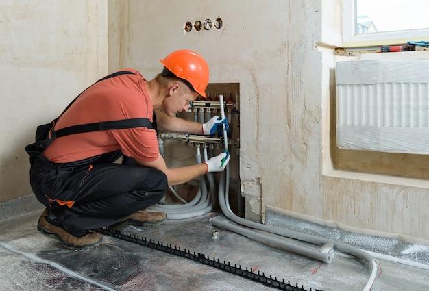 Рабочий устанавливает трубу для теплого пола в квартире