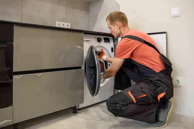 주방 가구에 세탁기를 설치하는 작업자