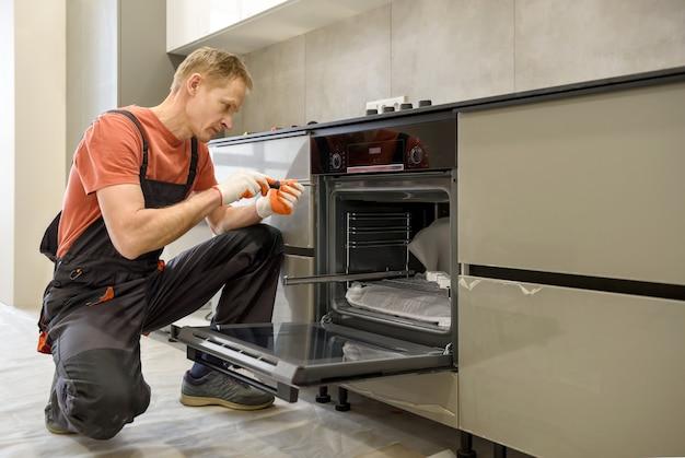 Рабочий, устанавливающий электрическую духовку в кухонной мебели