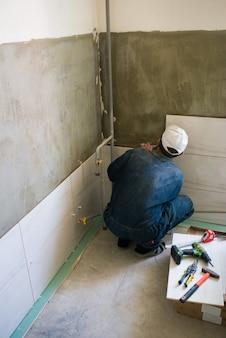 Рабочий устанавливает большие керамические плитки на стены