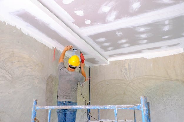 Worker installing board ceiling