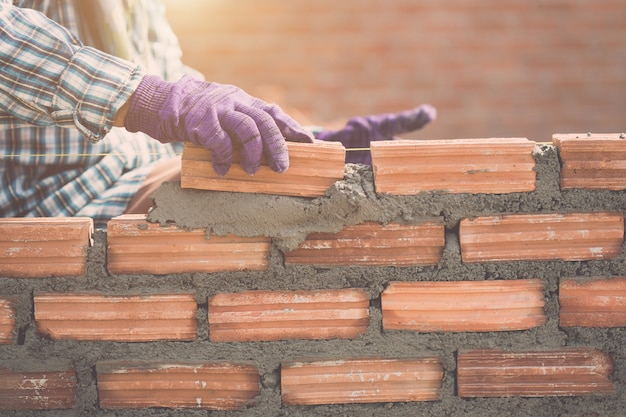 Worker installing bricks wall in process of house building