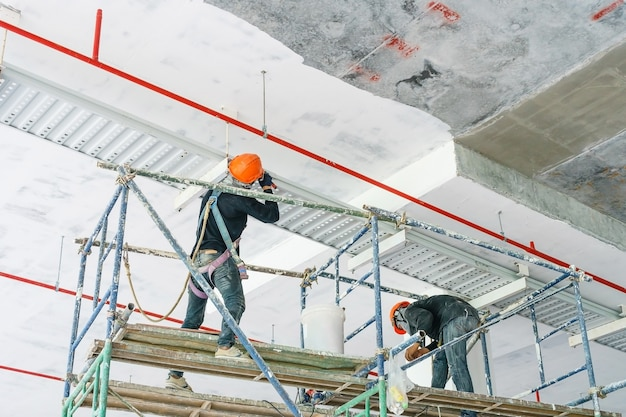 Worker installing cable tray with electrical wiring arrange on ceiling at offshore platfor