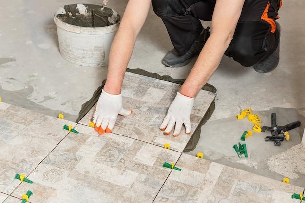 床にセラミックタイルを設置する労働者
