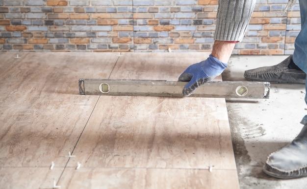 Рабочий устанавливает керамическую плитку с помощью уровня.