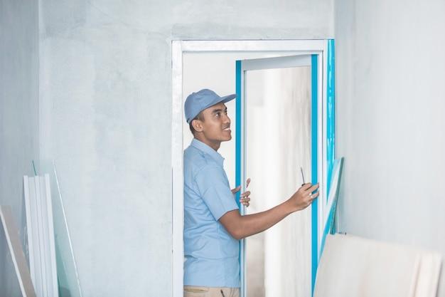 Рабочий, устанавливающий двери