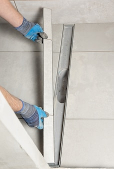 Worker installing a drain lid decorated with ceramic tiles in the bathroom