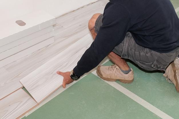 Рабочий, установка ламинированного деревянного пола в помещении, крупным планом.