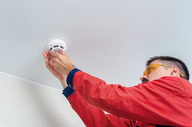 Рабочий, устанавливающий детектор дыма на потолке