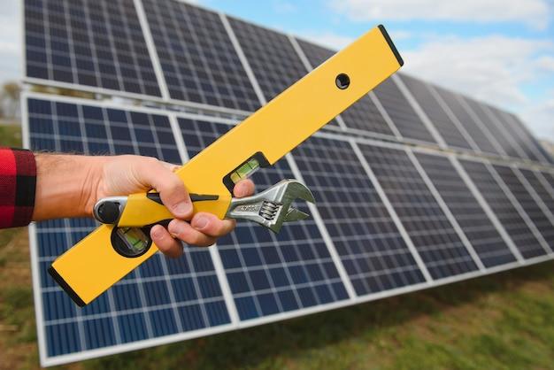 Рабочий, устанавливающий солнечные панели на открытом воздухе