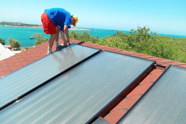 Рабочий устанавливает солнечные батареи на крыше дома.