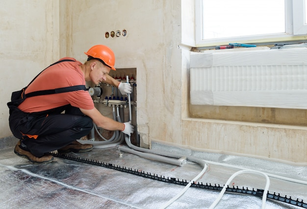 Worker installing a warm floor