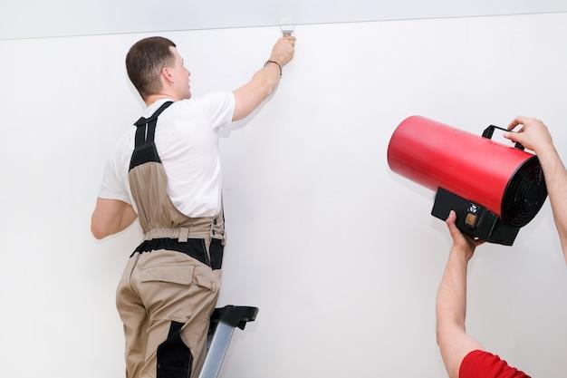 Рабочий устанавливает натяжной потолок. концепция строительства и ремонта