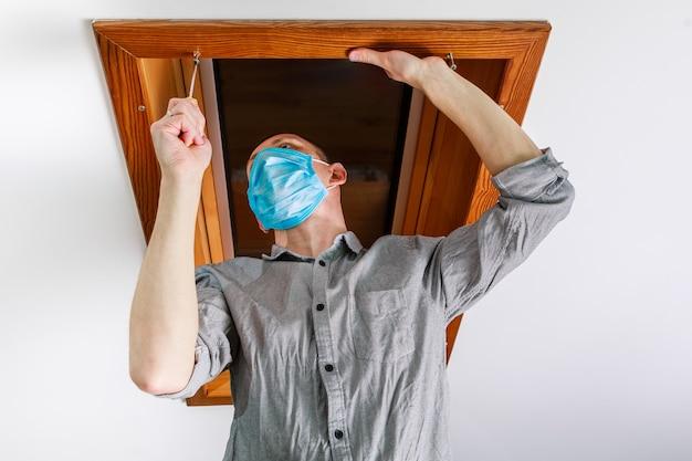 작업자가 집의 지붕 창을 설치하고 확인합니다.