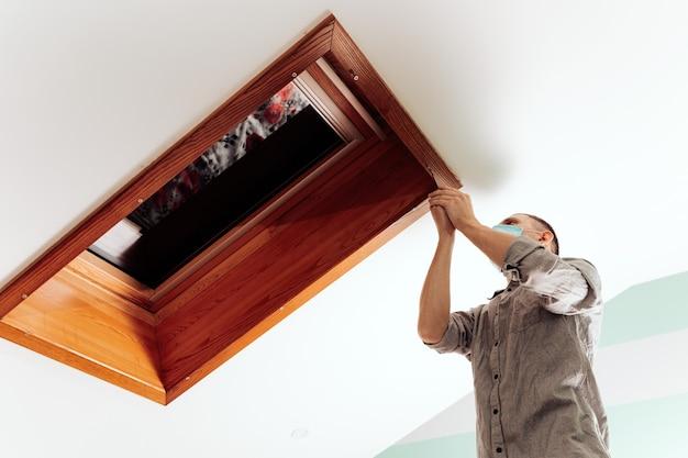 Рабочий устанавливает и проверяет мансардное окно в доме