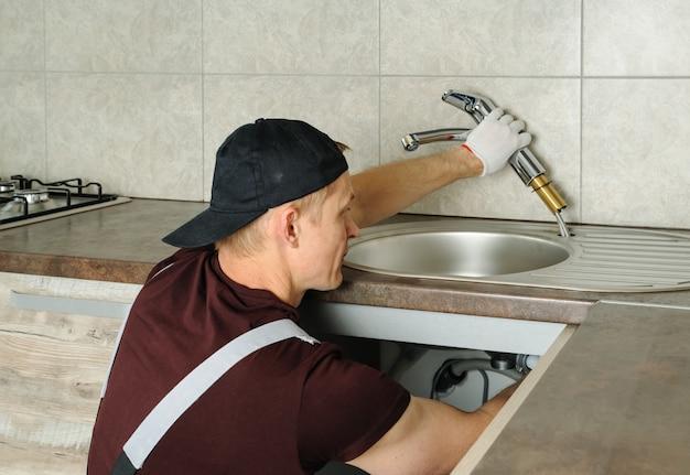 労働者は台所の流しの蛇口をインストールします