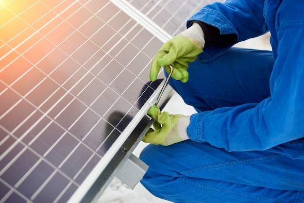 Worker installs solar batteries using tools in snow-covered weather