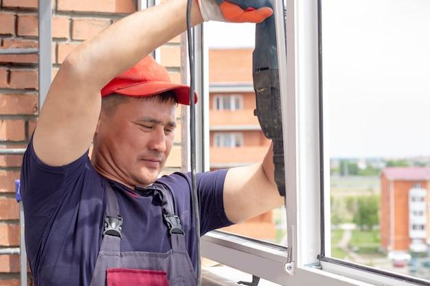 Работник устанавливает оконную мастерскую свердит раму для прикрепления к базе ремонта