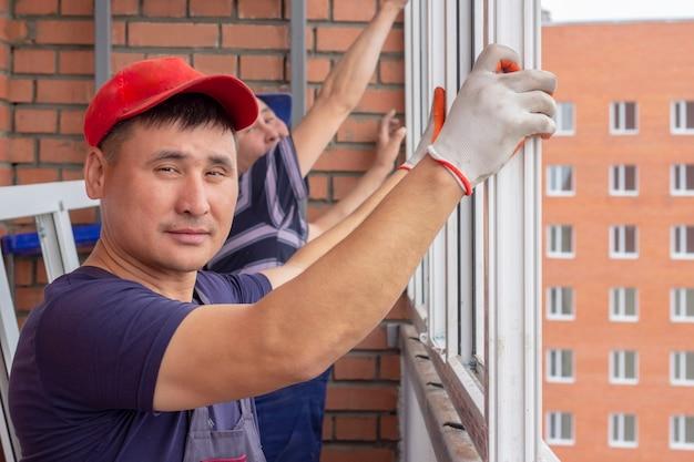 Рабочий устанавливает окна в многоэтажном доме