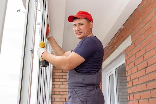 Рабочий устанавливает окна мастер свердит раму для прикрепления к основанию ремонта в многоэтажном доме.