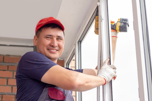 Рабочий устанавливает окна мастер свердит раму, чтобы прикрепить к основному ремонту в многоэтажном доме.